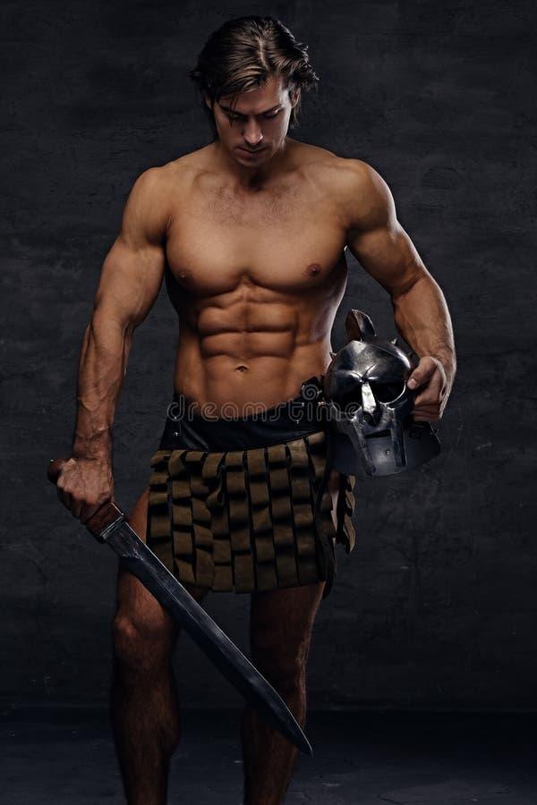 Het portret van shirtless spiermannetje houdt zilveren gladiator helme royalty-vrije stock foto's