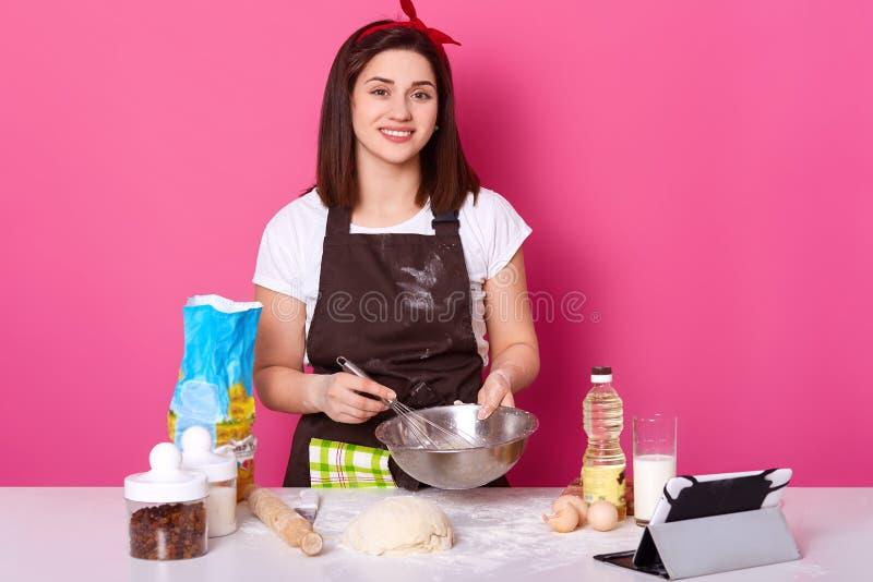 Het portret van slanke bekwame aantrekkelijke kok die zich bij keuken bevinden, mengt ingrediënten met zwaait, direct bekijkend  stock afbeeldingen