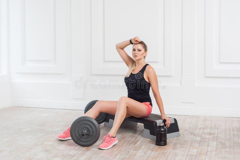 Het portret van sportieve mooie jonge atletische blondevrouw in roze borrels en de zwarte bovenkant worden hard gezweet en hebben royalty-vrije stock afbeelding