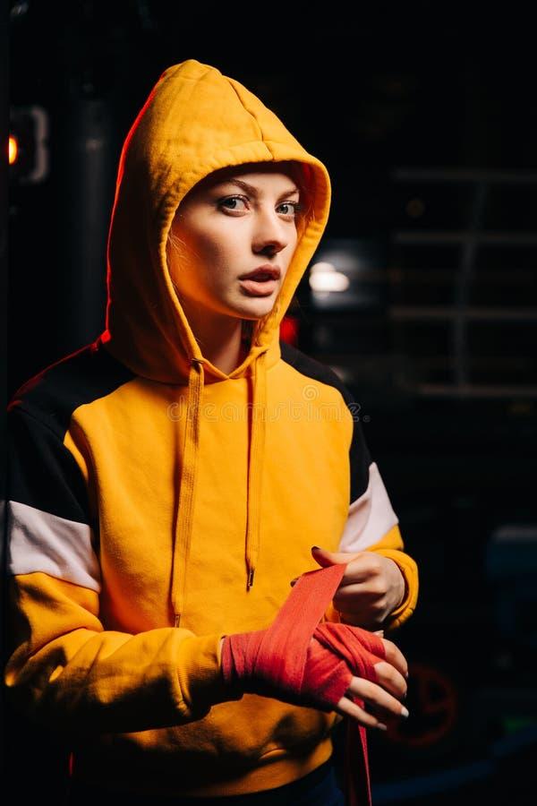 Het portret van sportvrouwbokser in geel sweatshirt trekt rode verbanden op haar handen, stock afbeelding