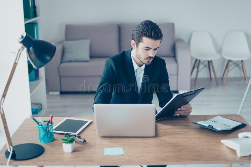 Het portret van succesvolle jonge manager in het formalwear gebruiken verwerkt gegevens stock foto