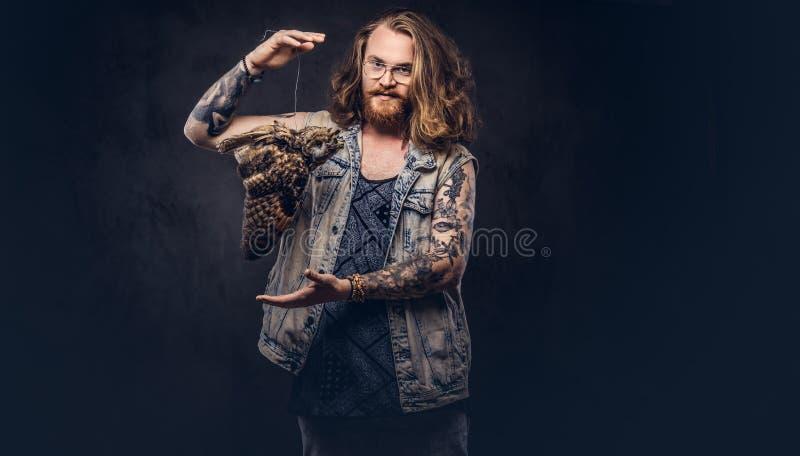 Het portret van a tattoed roodharige hipster mannetje met lang luxuriant haar en de volledige baard kleedde zich in een t-shirt e royalty-vrije stock fotografie