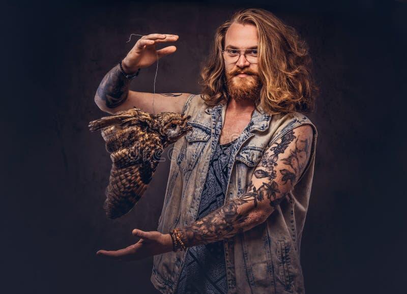 Het portret van a tattoed roodharige hipster mannetje met lang luxuriant haar en de volledige baard kleedde zich in een t-shirt e royalty-vrije stock foto