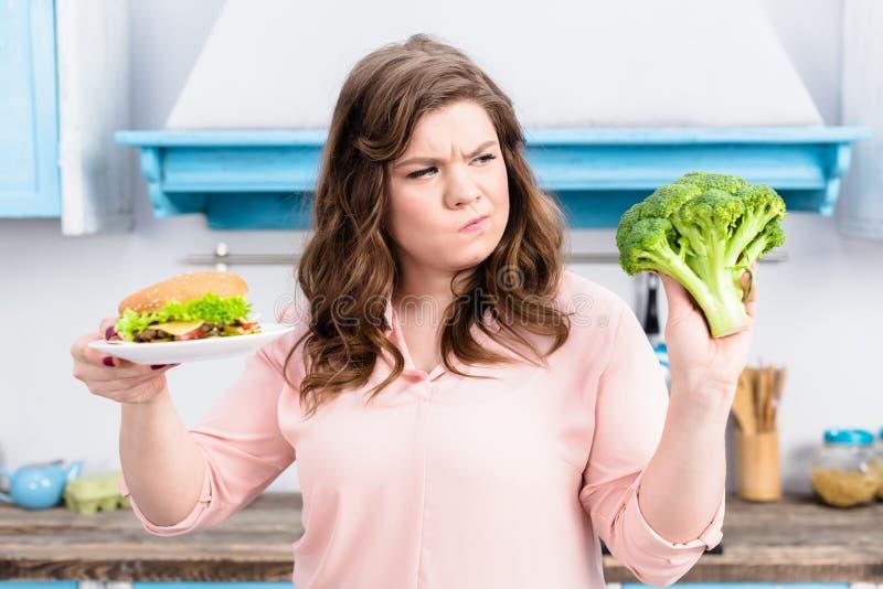 het portret van te zware vrouw met hamburger en verse broccoli dient binnen gezonde keuken in thuis, stock fotografie