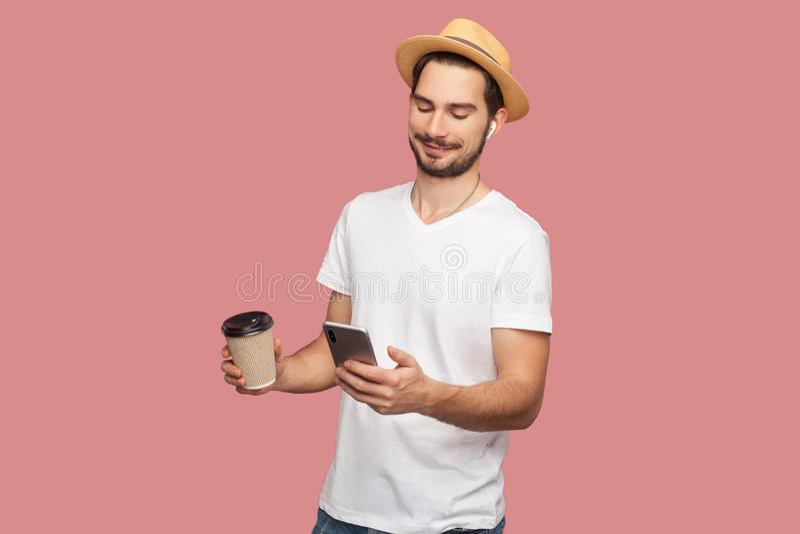 Het portret van tevreden knappe gebaarde jonge hipster blogger bemant in wit overhemd en toevallige hoed die zich met koffie en h stock foto