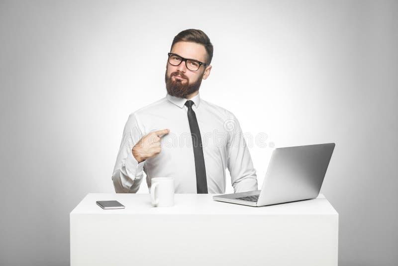 Het portret van tevreden zekere glimlachende gebaarde jonge manager in wit overhemd en de avondkleding zitten in bureau zijn prou royalty-vrije stock afbeelding
