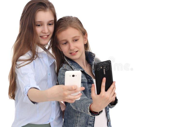 Het portret van twee vrolijke meisjes, meisjes neemt een selfie stock afbeeldingen