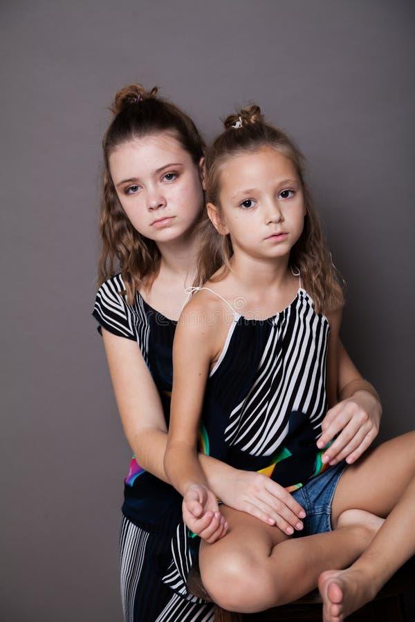Het portret van twee zustersmeisjes op een grijze achtergrond royalty-vrije stock foto