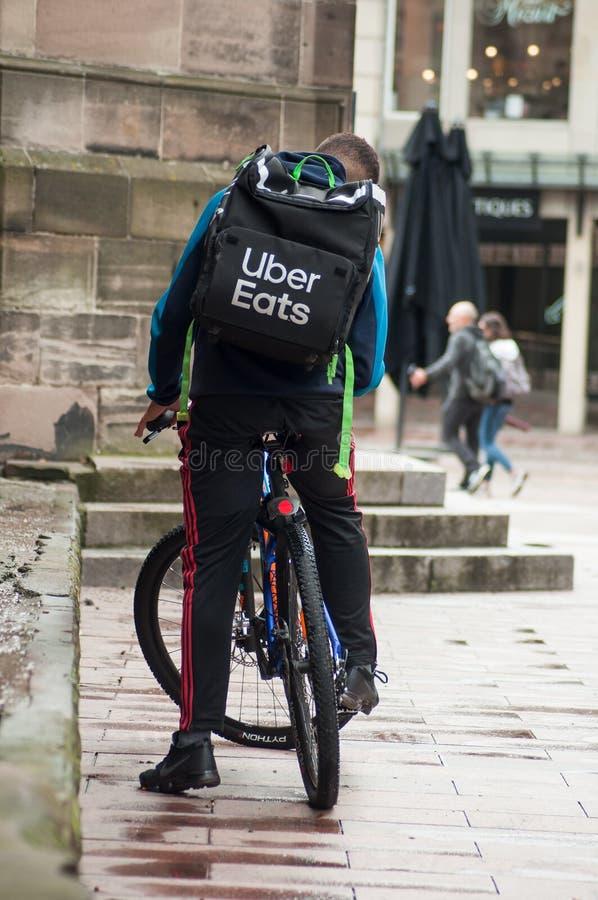 Het portret van uber eet de leveringsmens die in fiets in de straat wachten royalty-vrije stock fotografie