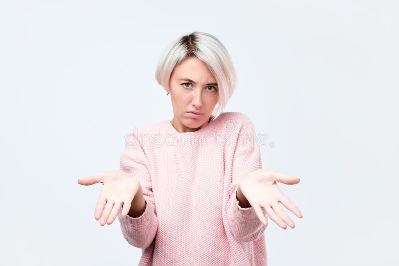 Het portret van verstoorde jonge toevallige meisje het uitrekken zich wapens aan u die het is uw probleem vertellen stock fotografie