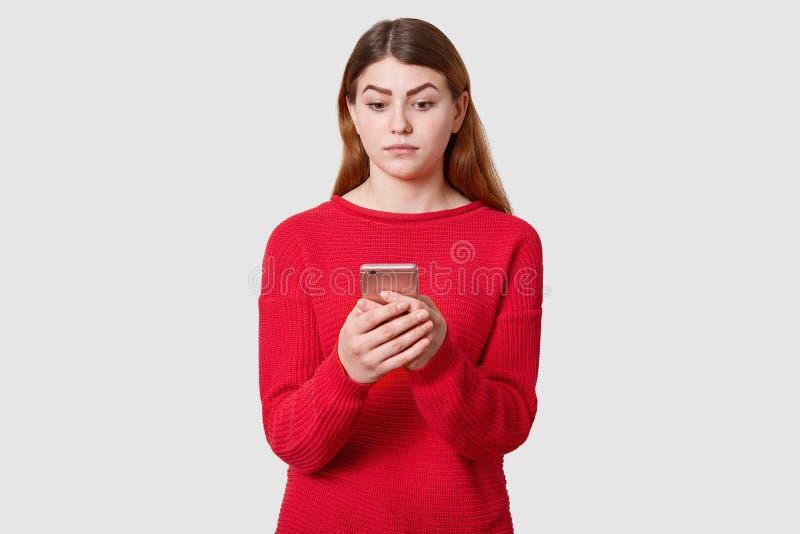 Het portret van verwarde leuke vrouw met donker recht haar, draagt rode sweater, houdt mobiele telefoon in hand, bekijkend zijn v royalty-vrije stock foto's
