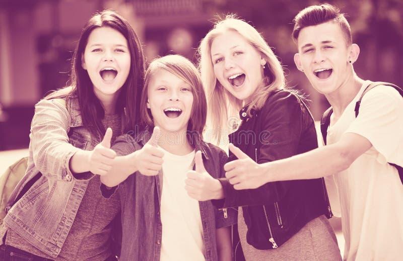 Het portret van vier het vrolijke tieners houden beduimelt omhoog stock afbeeldingen