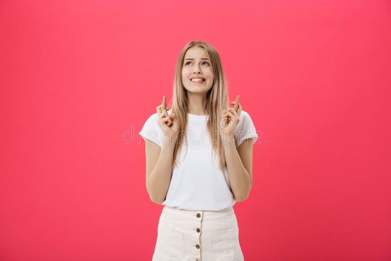 Het portret van vingers van een het glimlachen de toevallige meisjesholding kruiste voor goed die geluk over roze achtergrond wor stock fotografie