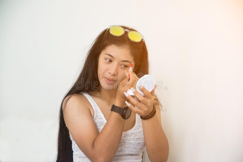 Het portret van vrij Aziatische vrouw is maakt omhoog oogschaduw met haar ogen en rode lippenstift van toepassing stock foto's