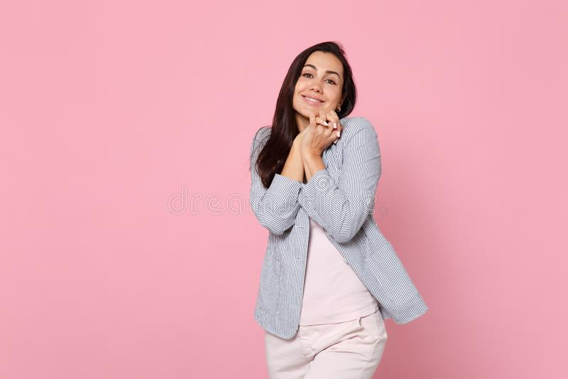 Het portret van vrij glimlachende jonge vrouw in de gestreepte palmen van de jasje bevindende holding vouwde geïsoleerd op roze p stock foto's