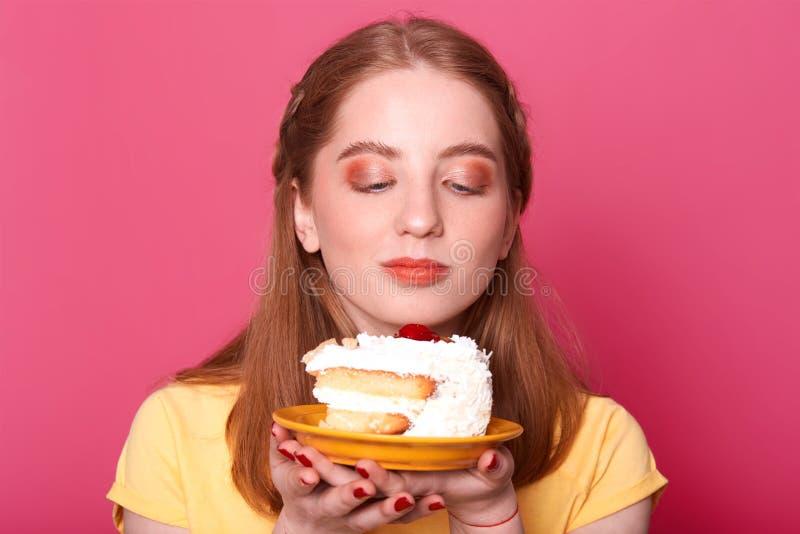 Het portret van vrij jong meisje, bekijkt plaat met stuk van verjaardagscake over roze achtergrond, wil smakelijk eten stock afbeeldingen