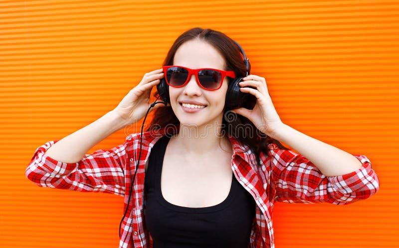 Het portret van vrij jonge vrouw luistert aan muziek in hoofdtelefoons royalty-vrije stock fotografie
