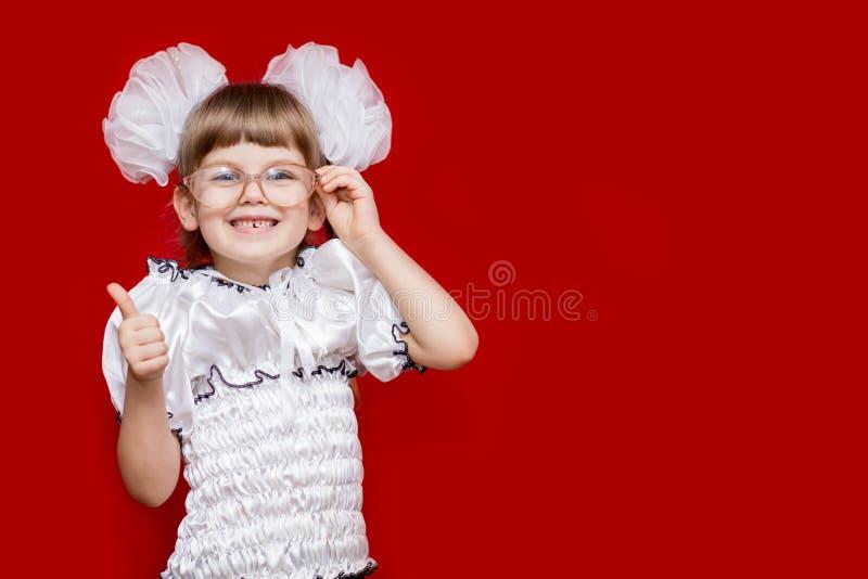 Het portret van vrolijk meisje in zeer grote glazen en de witte bogen tonen duim royalty-vrije stock fotografie