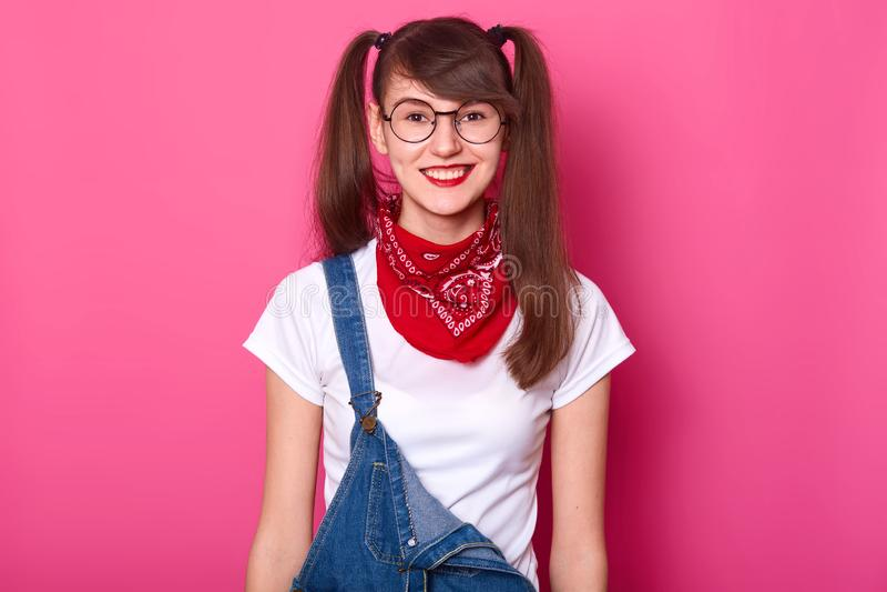 Het portret van vrolijk mooi meisje met lange vlechten, draagt t-shirt, denimoverall en rode bandana op hals aantrekkelijk royalty-vrije stock afbeelding