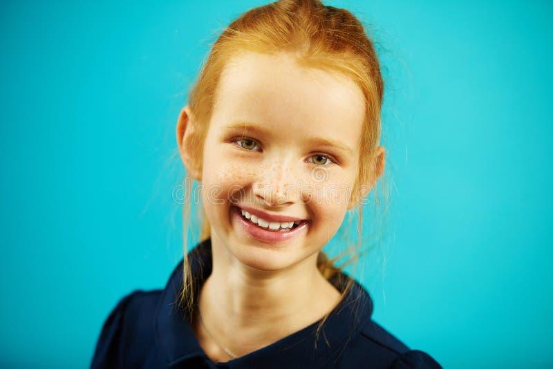 Het portret van vrolijk redheaded schoolmeisje van zeven jaar oud op blauw isoleerde achtergrond Blij kind met echt stock foto's