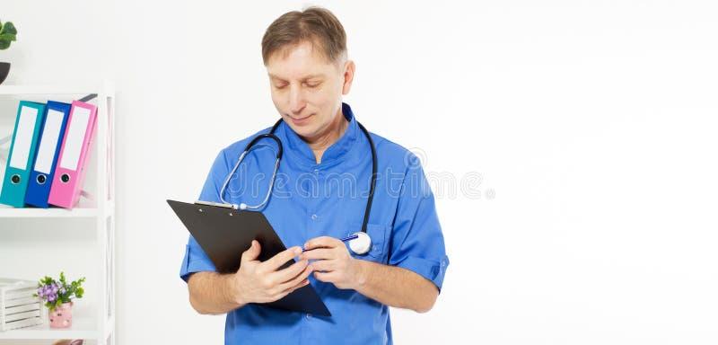 Het portret van vrolijke gelukkige mannelijke arts in het ziekenhuis neemt nota's Chirurg met stethoscoop op witte achtergrond Me royalty-vrije stock foto