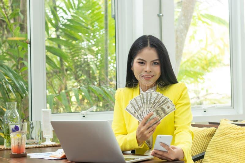 Het portret van vrolijke jonge Aziatische het geldbankbiljetten van de vrouwenholding en de mobiele telefoon met glimlach zien vo royalty-vrije stock foto's