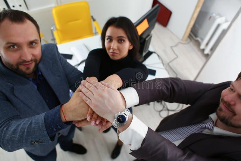 Het portret van vrolijke jonge zakenlieden in bureau plaatst hun handen over andere stock afbeelding