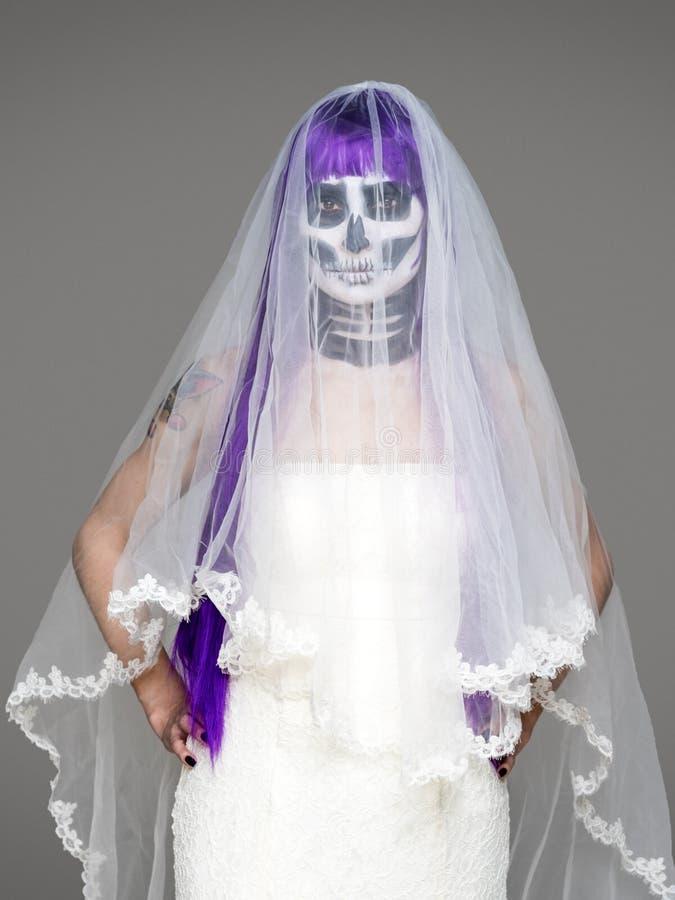 Het portret van vrouw bekijkt de camera met het angst aanjagen Halloween skeletmake-up en purpere pruikenbruidssluier, huwelijksk stock afbeelding