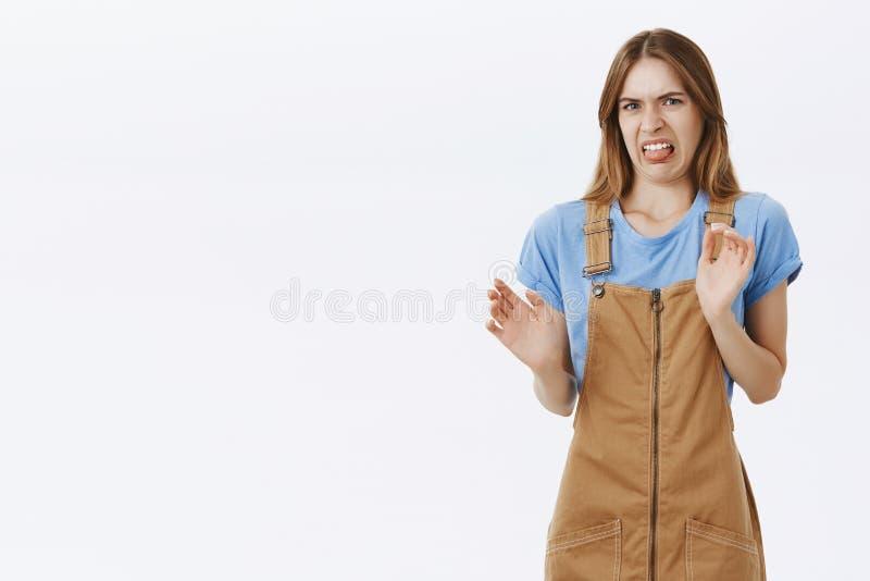 Het portret van vrouw die afkeer uitdrukken en houdt van niet plakkend uit tong van afschuw die braaksel willen opheffend palmen  stock afbeeldingen