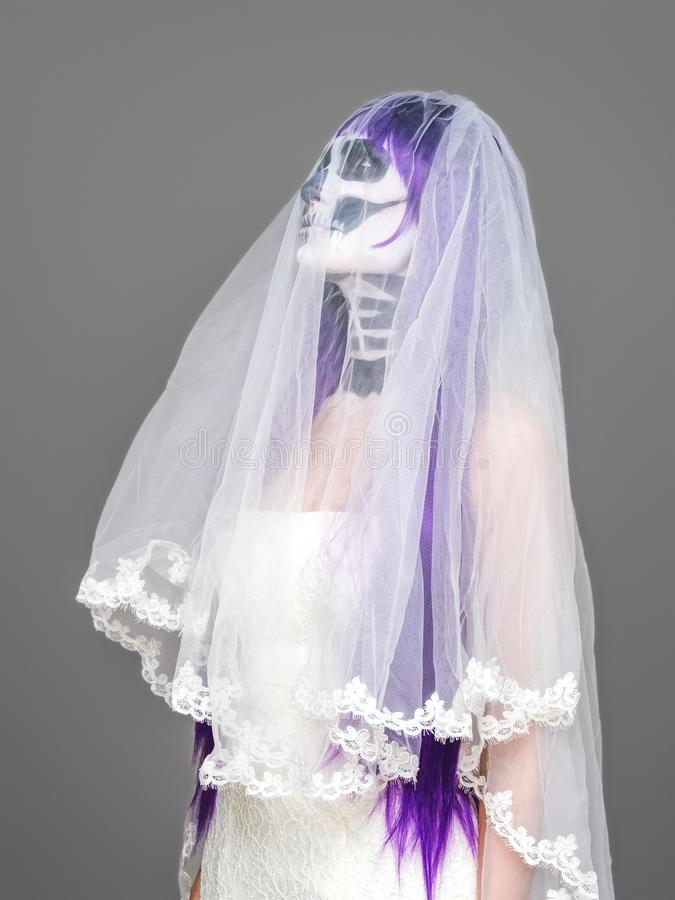 Het portret van vrouw kijkt upwards met het angst aanjagen Halloween skeletmake-up en purpere pruikenbruidssluier, huwelijkskledi stock fotografie