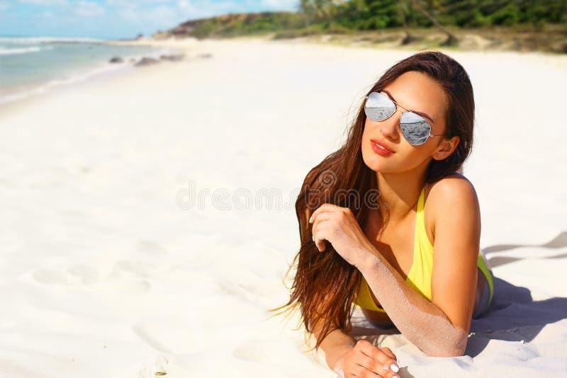 Het portret van vrouw zwemt kostuum binnen het ontspannen op tropisch strand stock afbeelding