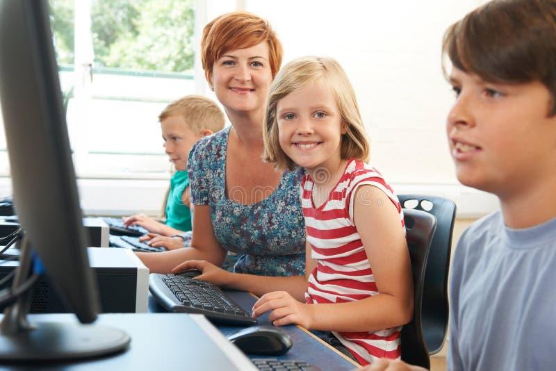 Het portret van Vrouwelijke Elementaire Leerling in Computerklasse met onderwijst stock foto