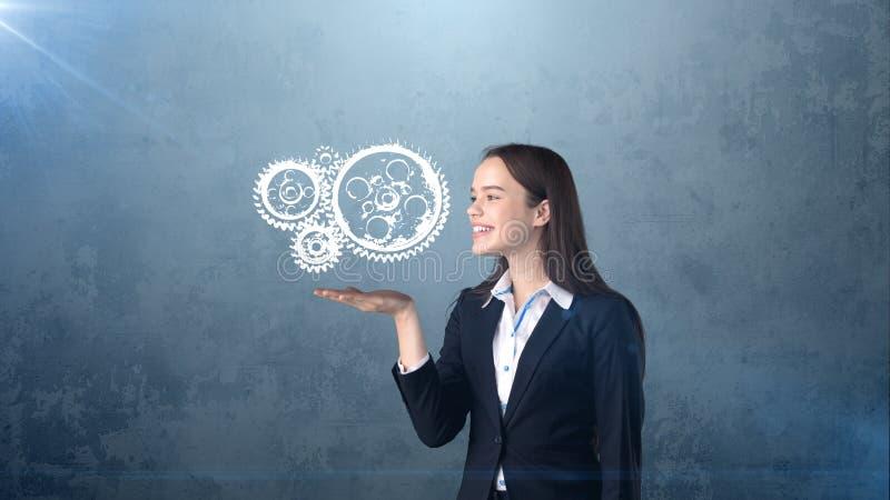 Het portret van vrouwenholding schilderde horlogemechanisme op de open handpalm, geïsoleerde studioachtergrond Bedrijfs concept royalty-vrije stock afbeeldingen