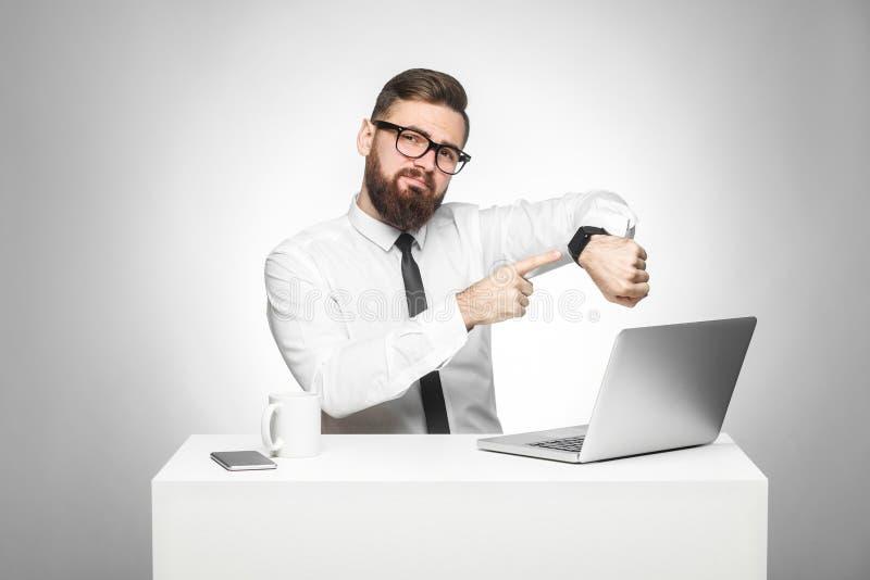 Het portret van het waarschuwen van knappe gebaarde jonge werkgever in witte overhemd en avondkleding zit in bureau en richt ving royalty-vrije stock foto
