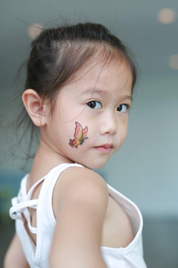 Het portret van weinig Aziatisch kindmeisje met de sticker van de vlindertatoegering op lichaamshuid, kleedt omhoog tatoegering royalty-vrije stock fotografie
