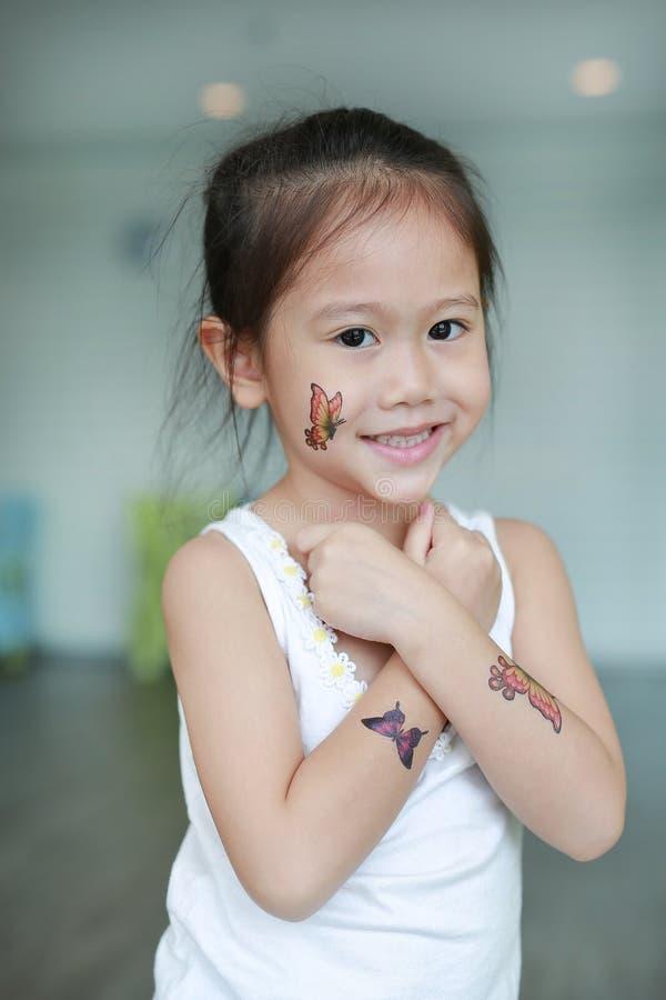 Het portret van weinig Aziatisch kindmeisje met de sticker van de vlindertatoegering op lichaamshuid, kleedt omhoog tatoegering royalty-vrije stock foto