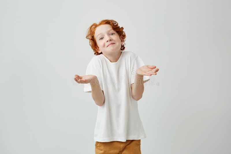 Het portret van weinig jong geitje met helder rood haar het mooi gesticuleren met handen tonen trekt ` t kent aan antwoord op ler royalty-vrije stock foto's