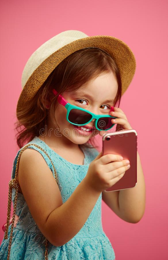 Het portret van weinig Kaukasisch meisje die in een strohoed en zonnebril, telefoon houden, heeft een vrolijke stemming oprecht g stock foto's