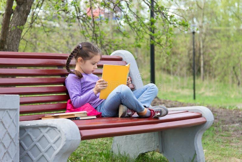 Het portret van weinig leuk meisje met open boek zit op de houten bank royalty-vrije stock foto's