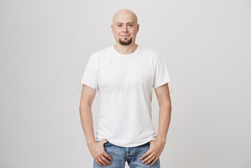 Het portret van zekere knappe kale Kaukasische kerel die toevallige t-shirt dragen en de jeans, het houden dienen zakken in royalty-vrije stock afbeeldingen