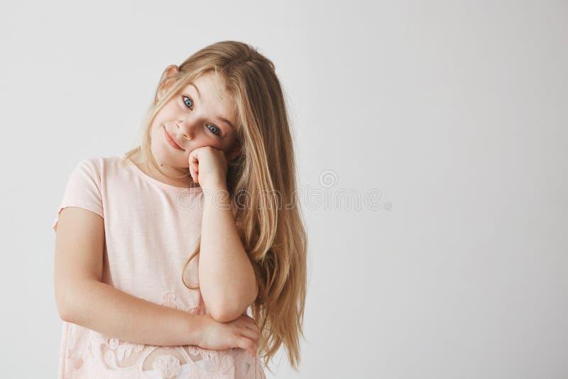 Het portret van zoet klein meisje met licht lang haar kleedde zich in roze t-shirt kijkend in camera met blije blik, het houden stock fotografie