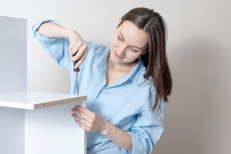 Het portretclose-up van een jonge onafhankelijke vrouw met een schroevedraaier verzamelt meubilair stock fotografie