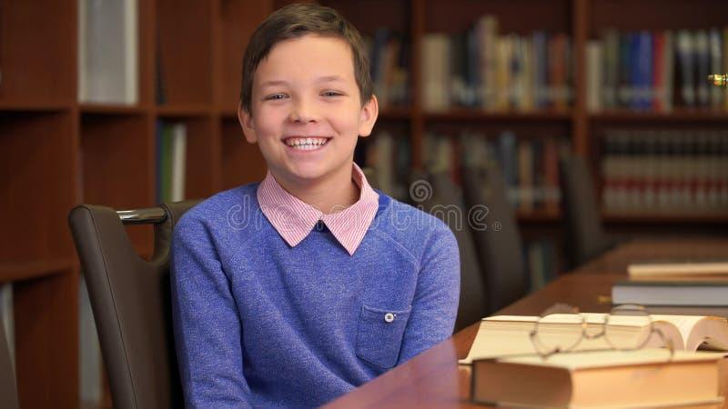 Het portretschot van de leuke schooljongen zit dichtbij het boekenrek in de bibliotheek royalty-vrije stock afbeelding