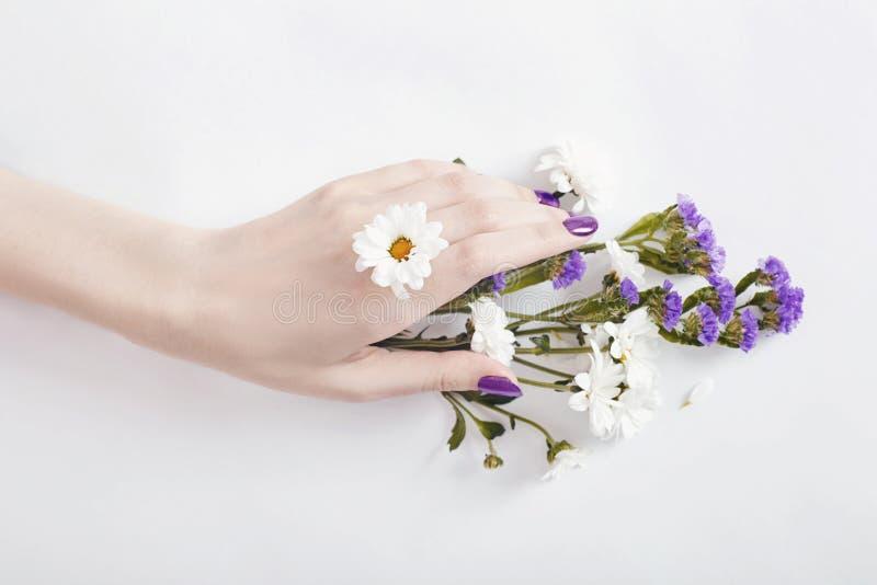 Het portretvrouw van de manierkunst in de zomerkleding en bloemen in haar hand met een heldere het tegenover elkaar stellen make- stock afbeeldingen