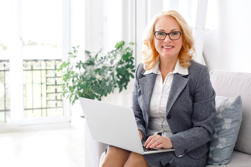 Het portretzitting van de vrouwenpsycholoog op toevallig huiskantoor die laptop met behulp van die camera kijken royalty-vrije stock foto's