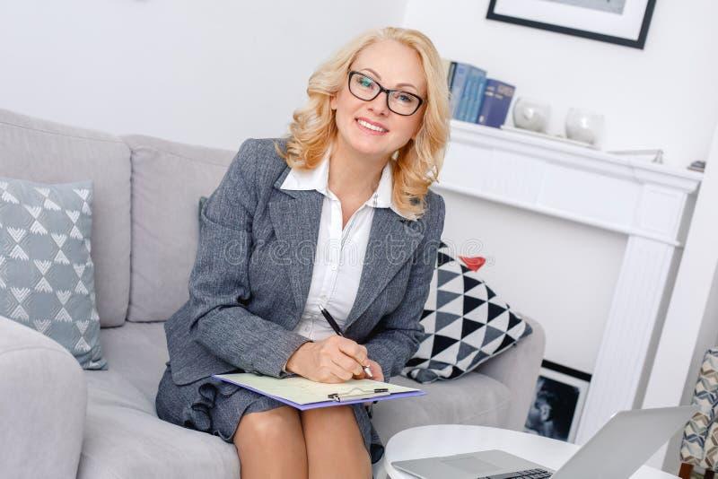 Het portretzitting van de vrouwenpsycholoog op toevallig huiskantoor die nota's het glimlachen nemen royalty-vrije stock fotografie