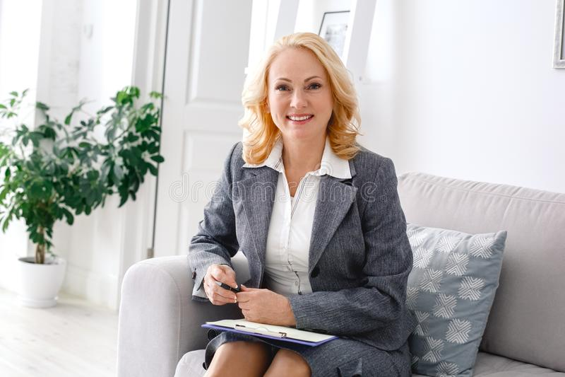 Het portretzitting van de vrouwenpsycholoog op toevallig huiskantoor met document houder stock foto