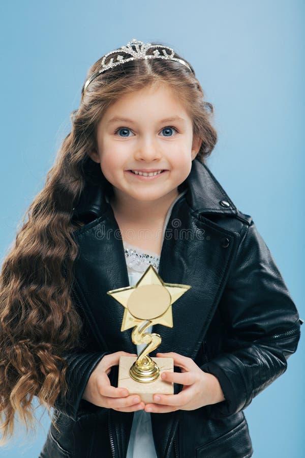 Het positief die Europees kind met blauwe ogen glimlachen, lang kernachtig haar, houdt beloning in vorm van ster, draagt zwart le royalty-vrije stock foto
