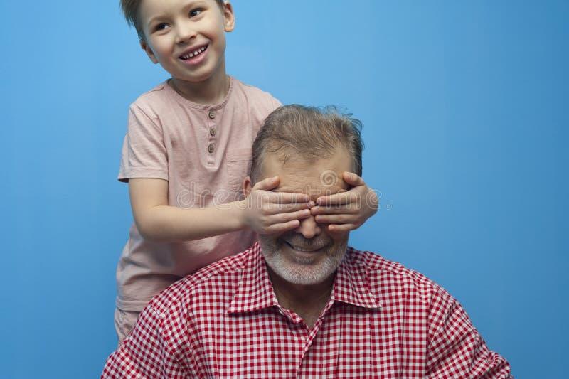 Het positief weinig jongen sluit ogen aan zijn grootvader stock foto's