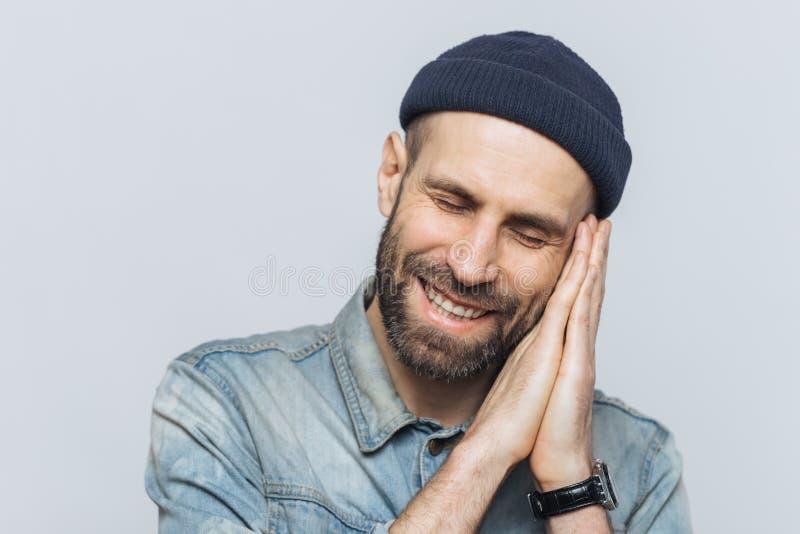 Het positieve gebaarde mannetje beweert slaap, heeft prettige dromen, rust op handen, vreugdevol glimlacht, draagt zwarte modieuz royalty-vrije stock foto's